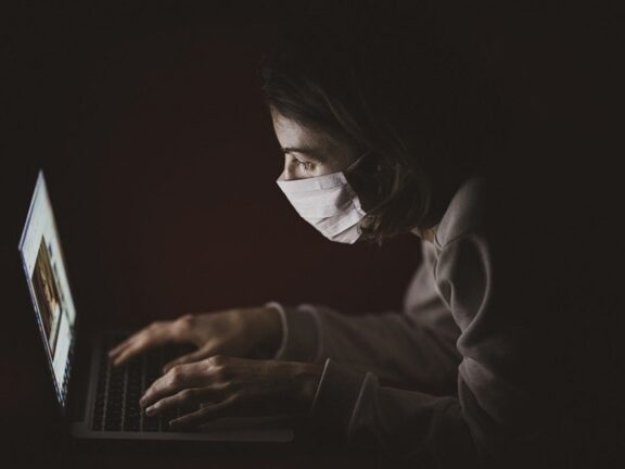 girl with a mask using computer